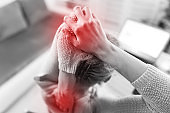 Woman working on a laptop and having hand, back, spine pain.