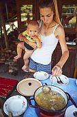 Woman with baby preparing food and feast for summertime lunch at countryside rustic cottage outdoor kitchen.