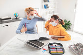 Child home studying education, homeschooling, with private tutor / mother with protective mask in the time of viruses, flu and seasonal pandemic, healthy approach in social contact.