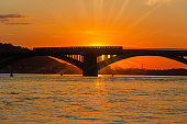 Silhouette of bridge across river at sunset in backlight