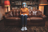 Woman with protective antiviral mask sitting at home in isolation / quarantine.