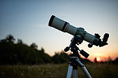 Telescope for observing the universe on a meadow outdoors.