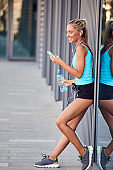Modern sportswoman making pause after jogging in the urban area.