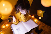 Young female child reading encyclopedia in a home made livingroom tent with light balls.