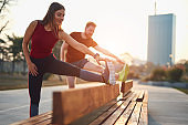 Two young sporty man and woman exercising in urban park.