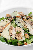 organic chicken caesar salad with parmesan cheese and croutons on white table background
