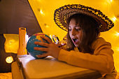 Young female child using magnifying glass to explore earth globe in a home made livingroom tent with light balls.