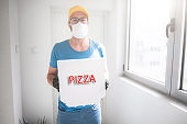 Deliveryman with protective medical mask holding pizza box - days of viruses and pandemic, food delivery to your home and safety hygiene measures.