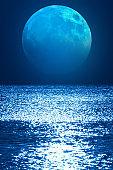 Full Moon rising above the ocean horizon.