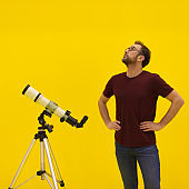Amateur astronomer looking at the stars with a telescope. Astronomy and astrology concept. Studio shot on a yellow background.