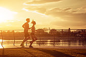 Modern woman and man jogging / exercising in urban surroundings near the river.