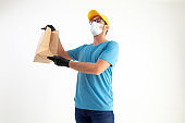 Delivery guy with protective mask holding paper bag with groceries.