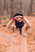 Young woman outdoors making heart - shape symbol for love and romance.