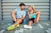 Modern couple making pause on the sidewalk during jogging / exercise.
