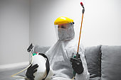 Person with protective antiviral mask, chemical decontamination sprayer bottle in home isolation.