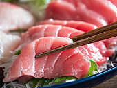 Close-up of tuna sashimi and chopsticks.