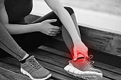 Young sportswoman having pain / injury during exercise and jogging in the park.