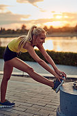 Young sporty woman stretching on a sidewalk near the river in sunrise / sunset time.