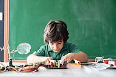 Elementary Schoolboy Working On Robotics And Coding In Front Of Green Chalkboard