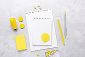Top view of workspace with notepad and stationery accessories on gray stone background. Illuminating Yellow and Ultimate Gray, colors of the year 2021