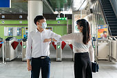 Elbow bump is new novel greeting to avoid the spread of coronavirus. Two Asian business friends meet in subway station. Instead of greeting with a hug or handshake, they bump elbows instead.