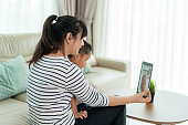 Asian young woman daughter and grandson virtual happy hour meeting and talking online together with her mother in video conference with tablet for a online meeting in video call for social distancing.