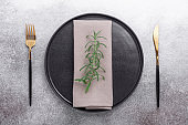 Table setting with empty plate, napkin, cutlery and rosemary on stone background Copy space Top view