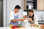 Young Asian love family are preparing food dinner on table in the kitchen which father and mother teaching daughter to cooking food on the day at home.