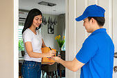 Asian delivery young man in blue uniform smile and holding smartphone in front house and Asian woman sign signature in smartphone to accepting a delivery of boxes from deliveryman.