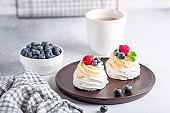 Coffee mug and Pavlova cake with whipped cream and fresh berries on wooden plate. Scandinavian style. Soft focus