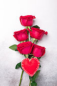 Valentines day greeting card. Red roses and decorative textile heart on stone background. Top view. Vertical