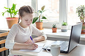 Schoolgirl studying at home using laptop. Home school, online education, home education, quarantine concept