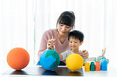 Asian preschool student boy with mother painting the moon learning about the solar system at home, Homeschooling and distance learning.