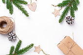 Christmas composition with fir tree branches, gift box and natural decor on white background