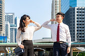 Elbow bump is new novel greeting to avoid the spread of coronavirus. Two Asian business friends meet in front of office building. Instead of greeting with a hug or handshake, they bump elbows instead.