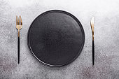 Empty black ceramic plate, fork and knife on stone background Copy space Top view