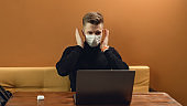 People with face mask. Concept with copy space. Portrait of young man who working with gray laptop. Photo indoor on yellow background.