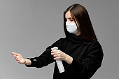 Young woman with antiseptic sanitizer and medical face mask at the studio with gray background. Girl wearing a black hoodie.