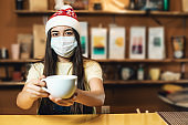 One cute woman with medical protective face mask working as bartender indoors cafe. Portrait with Christmas Santa Claus hat and cup of drink