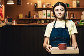 One cute woman working as bartender indoors cafe. Portrait of girl who prepare drinks for customer. Lady is holding cup of hot tea