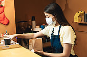 One cute woman with medical protective face mask working as bartender indoors cafe. Portrait with pack of coffee