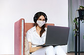 Nice adult woman with face mask indoors. She has casual eyeglasses. Concept photo with copy space. Portrait with laptop and headphones