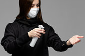 Young woman using antiseptic sanitizer on the hand.  Lady with medical face mask at the studio with gray background. Girl wearing a black hoodie.