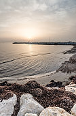 Sunrise at Mediterranean sea in spring with boulders at the foreground and concrete pier at the horizon line. Larnaka, Cyprus