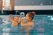 Mother and little son having fun in a swimming pool