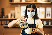 One cute woman working as bartender indoors cafe. Portrait with facial protective facemask. Girl prepare coffee for client