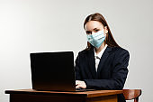 Portrait of young girl with facemask. Lady wear protective facial mask at the studio with gray isolated background. Woman is working on laptop