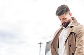 Portrait of bearded handsome man in beige jacket and white shirt outdoors. Business concept with copy space on the urban street. Photo with wireless earphones