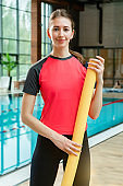Portrait of adult woman in the swimming pool.  Professional fitness instructor with aerobics aquatic noodles