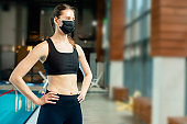 Portrait of aqua fitness instructor with medical protective facial face mask during coronavirus in swimming pool